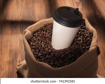 coffee paper cup in sackcloth bag on wood background.