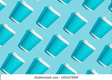Coffee pattern of blue paper cup for coffee on bright blue background. Pop art minimal flat lay style design, creative concept. Eco problem.Top view. Copy space. Banner.