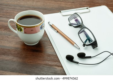 Coffee, pen, headphones and glasses on wood table. Wood texture