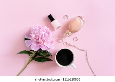 Coffee, peony, cosmetics and accessory on a pink pastel background