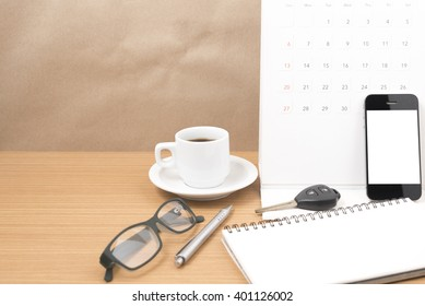 coffee and phone with car key,eyeglasses,notepad,calendar on wood background