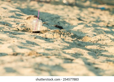 Coffee in a plastic cup with straw on a beach