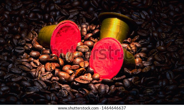 Coffee pods dropped into coffee beans with light focused on the pods