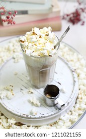 Coffee with popcorn.  A glass of coffee with milk and cream with the addition of popcorn.
