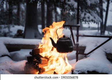 Coffee pot hanging over the fire outside in the winter. Winter theme. Camping, hiking concept.
