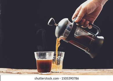 Coffee is poured into a cup from French press coffee maker , On the  old wood table and black background, Natural light, Selective focus, Vintage style.