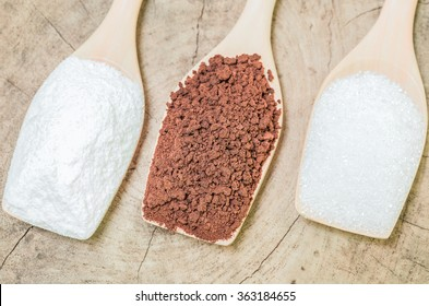 Coffee powder and creamer with sugar cubes on wooden spoon