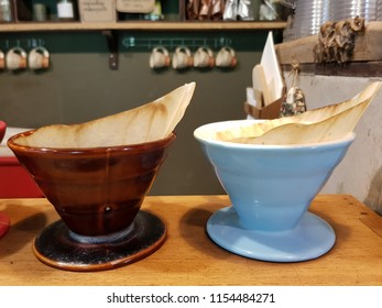 coffee powder and percolate  paper inside , there are cups hang on shelf in the