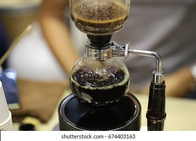 coffee preparation step by step. barista waits process of brewing coffee in a flask siphon. extraction process.  pouring siphon into the flask from the kettle of hot water