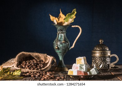 Coffee and Rahat Lokum. Tturkish coffee into traditional embossed metal cup. Cup of Coffee and burlap sack full of roasted beans s on wooden table closeup. Caffee aroma and rahat lokum