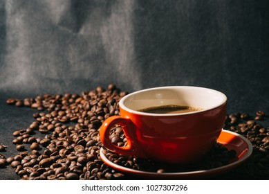 coffee in red cup and coffee beans are the background.