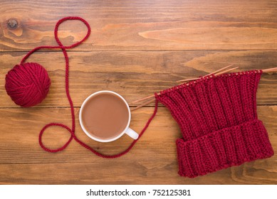 Coffee and red knitting on wooden background
