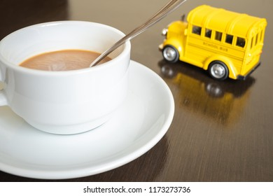 Coffee relaxing in office concept. Coffee cup and school bus on wooden desk at officce.