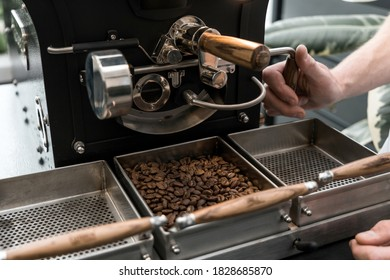 Coffee roster emptying the roaster and setting coffee beans to cool
