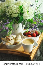 Coffee, rugelach with chocolate filling, strawberries and flowers on wooden tray.