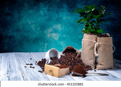 Coffee seeds in spoon with some jute bags filled with coffee beans