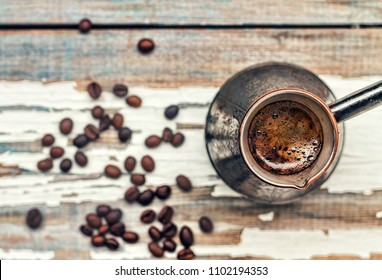 Coffee. Selective focus coffee in Turkish Cezve and grain on a white old windowsill, Closeup, top view, copy space