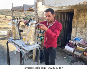 Coffee seller serving coffee, September 2017, Hermel, Lebanon: A young man  pours fresh coffee  in a cup from a traditional coffee maker outside his small road shop in Hermel, Lebanon