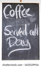 Coffee served all day sign written with chalk on blackboard