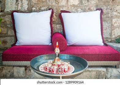 Coffee set on a table in front of sofa. Cup of tea on a tray on a round table with sofa in living room at home.