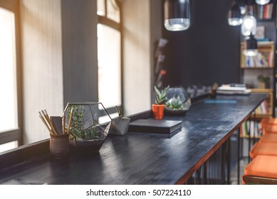 Coffee shop contemplation. Shot of high table with flowerpots on it in front of window of cafe