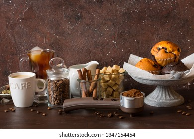 Coffee shop counter with cold brew coffee and latte with chocolate and blueberry muffins on cake ctand, cinnamon sticks, coffee beans and brown sugar cubes.
