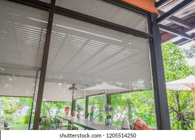 Coffee shop is a glass room with blind, curtain, roller, shade, shutter protected sunlight and green garden outside.
