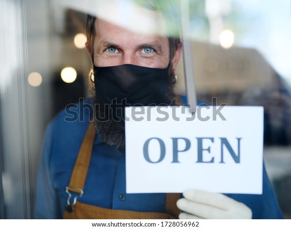 Coffee shop man owner with face mask, open after lockdown quarantine.