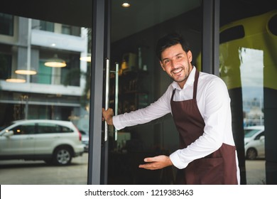 The coffee shop owner is opening the door, inviting customers to his shop. Setup studio shooting.