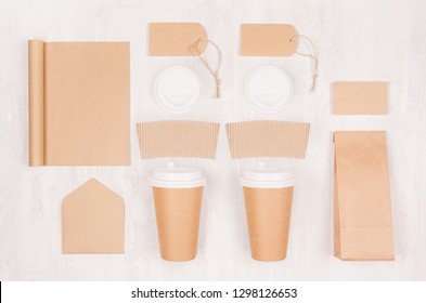 Coffee shop template for branding identity - two brown paper cups with blank notebook, packet, label, card, cap, envelope on white wood board, top view.