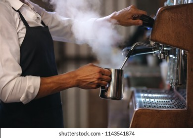 Coffee shop worker preparing coffee on steam espresso coffee machine. Cropped shot of man working in coffee shop wearing an apron.