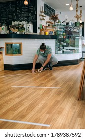 Coffee shop worker putting floor marks to keep social distance