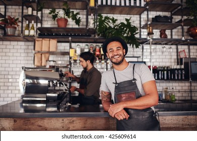 Coffee shop worker smiling to camera, standing at the counter. Happy young man in apron and hat leaning to cafe counter, with waiter working in background.