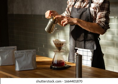 Coffee shop worker standing at the counter with hand drip coffee set