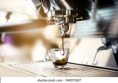 In coffee shop,coffee maker machine pouring hot fresh coffee into a cup of clear glass cup.