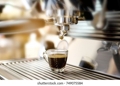 At coffee shop,coffee maker mechine pouring hot fresh coffee into a cup of clear glass cup. - Shutterstock ID 749075584