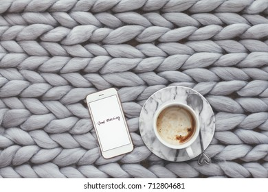 Coffee and smartphone on knitted woolen chunky blanket. Scandinavian home, minimalistic style, hygge, autumn morning cozy concept.