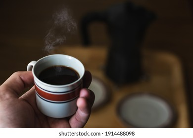 Coffee with smoke in a porcelain cup with unfocused background