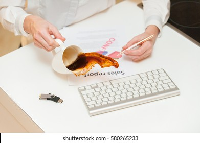 """Coffee spilled over modern keyboard and self made sheet of """"sales report"""""""