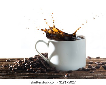 Coffee splash with heart shaped handle shadow and coffee beans on wood