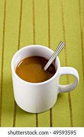 Coffee and Spoon in White Mug on Green Placemat