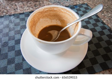 Coffee stains in a white cup with a spoon.