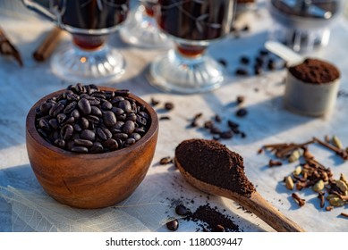 coffee still life above view of coffee in mugs, whole coffee beans, spoons of ground coffee, whole bean grinder