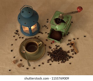Coffee Still life with coffee mill cup spoon sugar ground and unground coffee beans and candle lamp