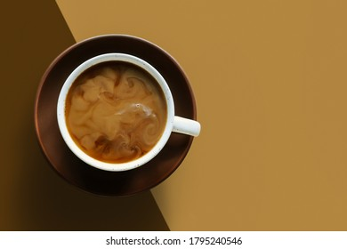 Coffee with swirl of milk or cream. Cup of morning drink, saucer on double diagonal background. Monochrome horizontal banner, poster with copy space. Chocolate brown, beige colors. Flat lay trend