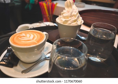coffee table with table decoration, two glasses of water, white glass vanilla ice cream, coffee specialty, coffeee with heart decoration on top , milky , whip cream.professional coffee service
