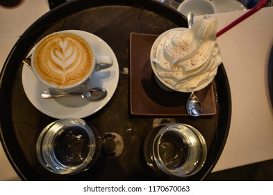 coffee table with table decoration, two glasses of water, white glass vanilla ice cream, coffee specialty, coffeee with heart decoration on top , milky ,