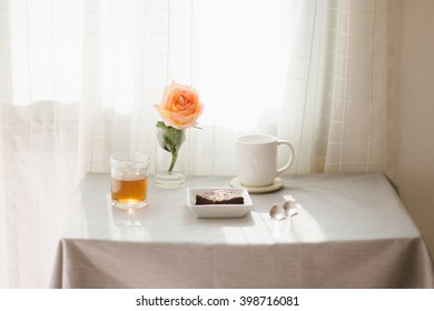 Coffee , tea and brownie on stripe tablecloth.
