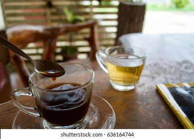 Coffee and tea in cup on wooden table.