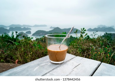 coffee or tea on table islands and mountains. Traditional Vietnamese coffee with condensed milk in a glass transparent glass on the background of beautiful landscape of Halong Bay in North of Vietnam.